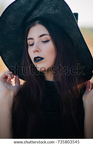 A young, beautiful girl with pale skin and black lips in the form of a witch for Halloween. A model with clean skin. #735803545