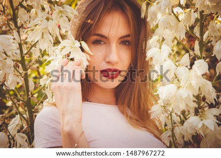 A young beautiful girl with red lips stands in flowering branches with white flowers. Fine art portrait.