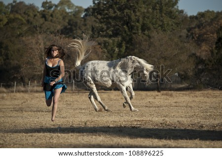 A young beautiful horse rider is playing catchers with her appaloosa gelding, while he playfully rears and bucks a few meters away from her, while she laughs.