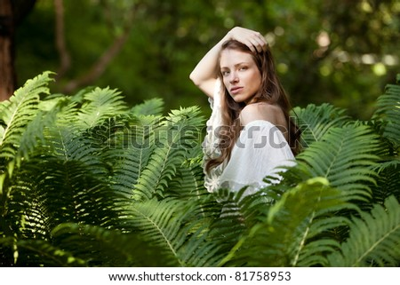 A young, beautiful lady hides and seeks in fern