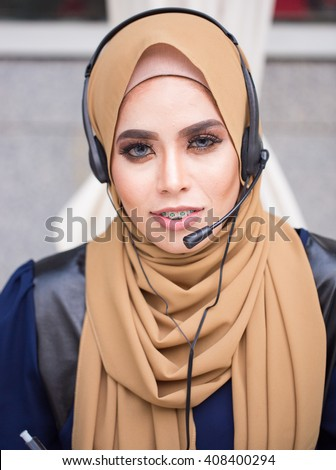 A young beautiful muslim woman working as a customer service, inside her office