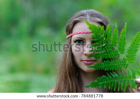 A young beautiful Slavic girl with long hair and Slavic ethnic dress covered her face with a large fern leaf