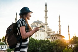 A young beautiful traveler girl in a hat with a backpack is watching a map next to the blue mosque - the famous sight of Istanbul. Travel, tourism, sightseeing.