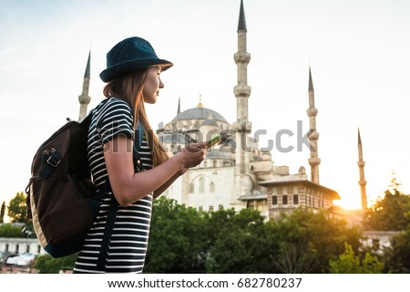 A young beautiful traveler girl in a hat with a backpack is watching a map next to the blue mosque - the famous sight of Istanbul. Travel, tourism, sightseeing. #682780237