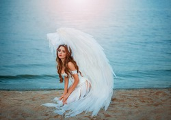 A young beautiful woman angel with white wings