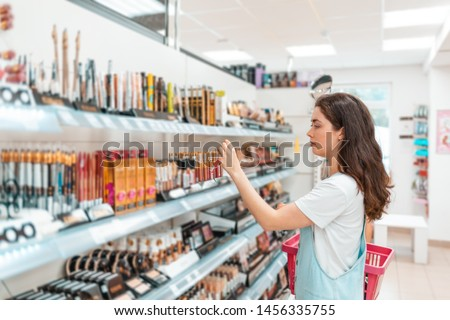 A young beautiful woman chooses lipstick in a cosmetics store. Purchase and sale of goods in supermarkets