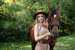 a young beautiful woman, dressed in a beige dress, holds a horse near herself against the backdrop of the forest.