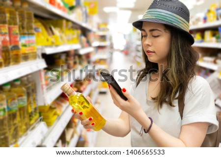 A young beautiful woman holds a bottle of oil in her hand and takes a picture of her on a mobile phone. In the background shelves with products. The concept of modern shopping in the store.