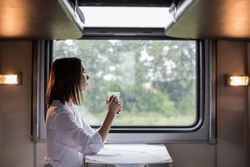 A young beautiful woman in a white shirt is sitting in a train compartment with a Cup of tea and looking out the window. Travel by train.