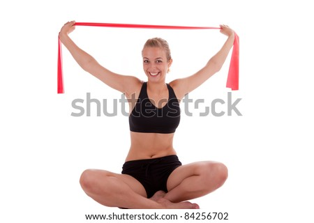 A young beautiful woman is doing exercises with a red stretch band