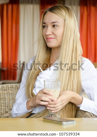 a young beautiful woman is drinking from a cup