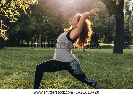 A young beautiful woman is meditating or practising yoga outdoors. Outdoor recreation concept.