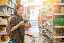 A young beautiful woman rolls a grocery cart and reads information about the selected product. Conscious consumption concept. Light. Close up.