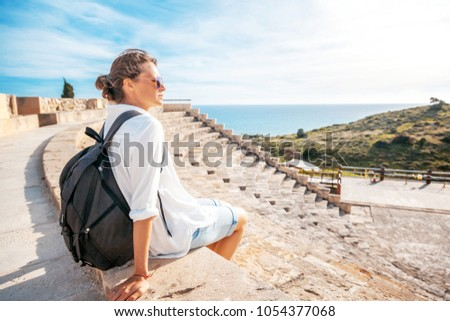 A young beautiful woman traveler sits on the steps of an amphitheater in an architectural antique museum overlooking the sea. A trip to antiquity, Cyprus, Park Kourion #1054377068
