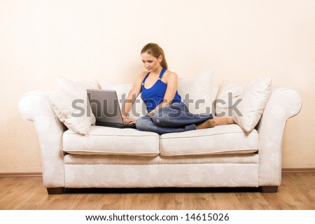 a young beautiful woman with a laptop on a lounge