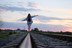 a young beauty walks along the railway at sunset, smiles and enjoys life