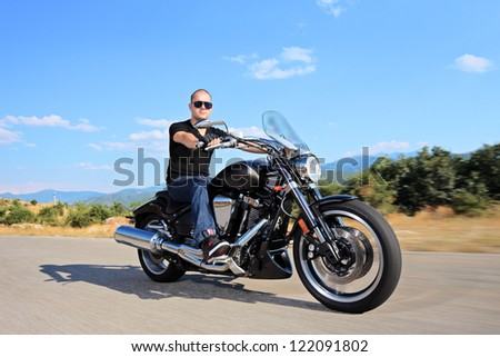 A young biker riding a customized motorcycle on an open road