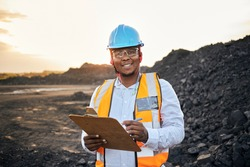 A young Black African coal mine foreman looking into camera smiling wearing reflective bib and hard hat is inspecting samples of coal on his clipboard after a long day of work on site at the coal mine