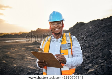 A young Black African coal mine foreman looking into camera smiling wearing reflective bib and hard hat is inspecting samples of coal on his clipboard after a long day of work on site at the coal mine Imagine de stoc ©
