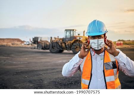 A young Black African coal mine foreman wearing reflective bib and hard hat is putting on a covid 19 face mask after a long day of work on site at the coal mine