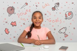 A young black African girl with a rapturous look is writing down her goals in a notebook.  Doodle about powers of the girl are drawn on the background. Happy childhood concept