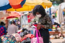 A young black African woman removing money from her purse to pay a local vendor - millennial wearing face mask for protection after lockdown during covid-19 pandemic