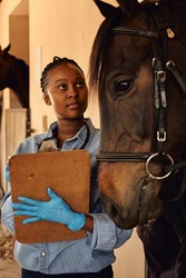 A young Black African woman veterinarian standing outside a horse stable holding a clipboard after checking the health of a horse.