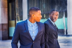 A young black businessman is standing by a mirror on the street and looking at the reflection. Concept of self assured, self esteem and self checking. A fine art lifestyle color photography.