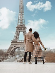 A young black couple, dressed in a plaid coat, stands in an embrace against the backdrop of the Eiffel Tower in Paris.