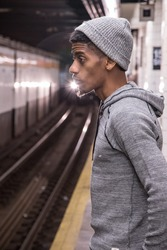 A young, black male waits for a New York City subway train. Shot during the autumn of 2016.