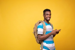 a young black man carrying a backpack using his mobile phone, smiling