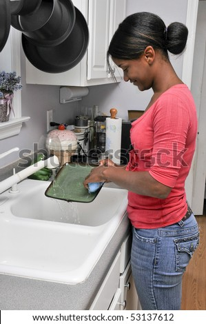 A young black woman doing the dishes