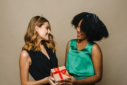 A young black woman is giving her Caucasian girlfriend a holiday gift. Concept of New Year, Birthday or Birthday