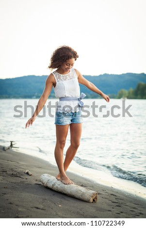 A young black woman stands on a beach by a river.