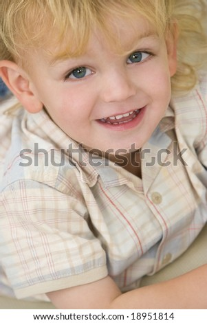 A young blond boy dressed laying down and giving a cheeky grin