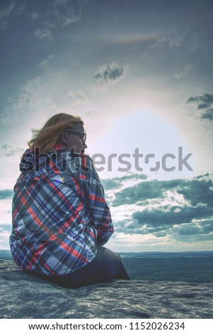 A young blond girl sit on peak and enjoy sun. Woman hiker watch sunrise or sunset while sitting on top of a mountain or on a large rock. Meditation in nature #1152026234