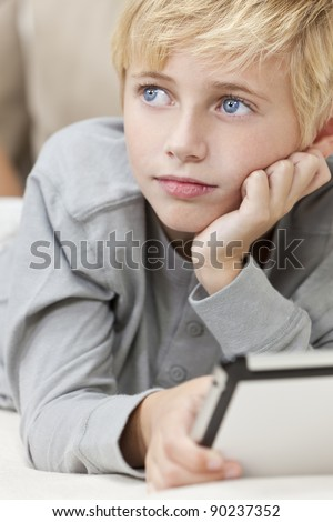 A young blond haired blue eyed boy child resting on his hands laying down on a sofa using tablet computer