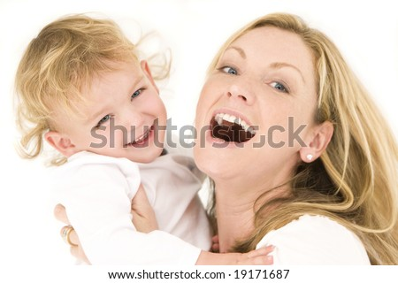 A young blond mother and her son dressed in white and having laughing together