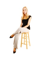 A young blond woman resting on a chair in a black blouse and light gray track pants for white background isolated in the studio.