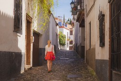 A young blonde female tourist explores the quaint and narrow cobblestone streets in old town (Albaicin or Arab Quarter) Granada, Spain, Andalusia.