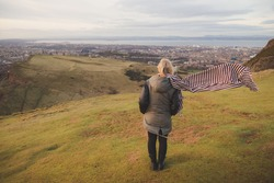 A young blonde female tourist with a scarf looks out to a cityscape view of Edinburgh, Scotland on a windy afternoon up Arthur's Seat in Holyrood Park.