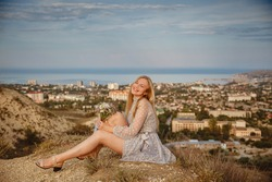 A young blonde girl in a gray dress sits on a hilltop overlooking the seaside town of Feodosia in Crimea in summer. High quality photo