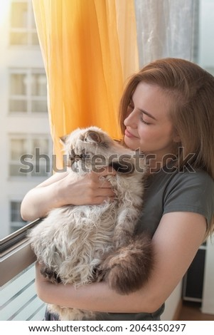 A young blonde girl is huging with love her Persian cat at the window of her house.