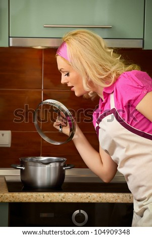 A young blonde girl prepares food on kitchen