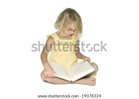 A young blonde girl sitting cross-legged while reading a textbook.  Isolated on a white background