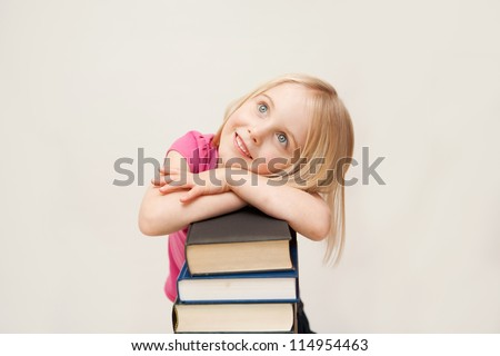 A young blonde girl with blue eyes is leaning over a pile of books.  The photo is taken against a white background