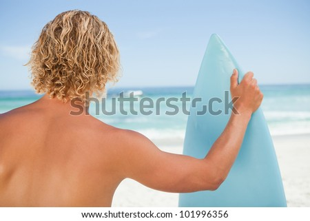 A young blonde man holding a perched surfboard while standing on the beach
