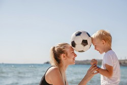 a young blonde mother with a blond son hold a ball between their heads in the summer on the sea coast. The theme of family sports