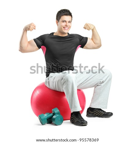 A young bodybuilder gesturing and seated on a pilates ball isolated against white background