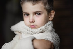 A young boy, a serious look is dressed in a knitted white sweater. Portrait
